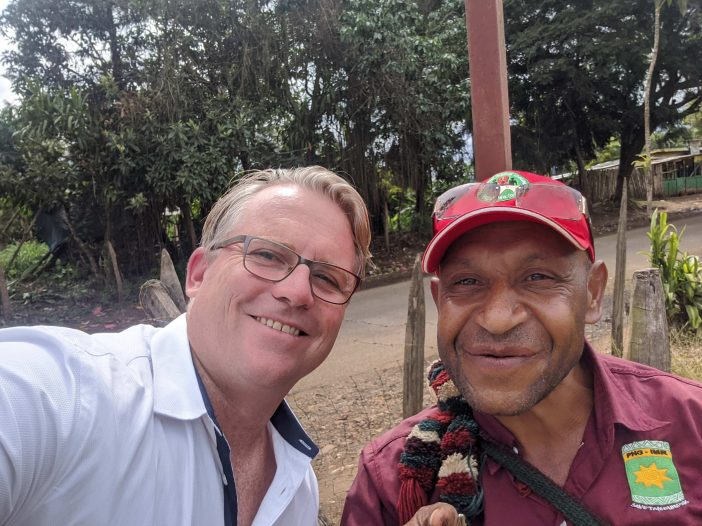 Ricky and his tour guide smile for the camera by the side of the road in Papua New Guinea.